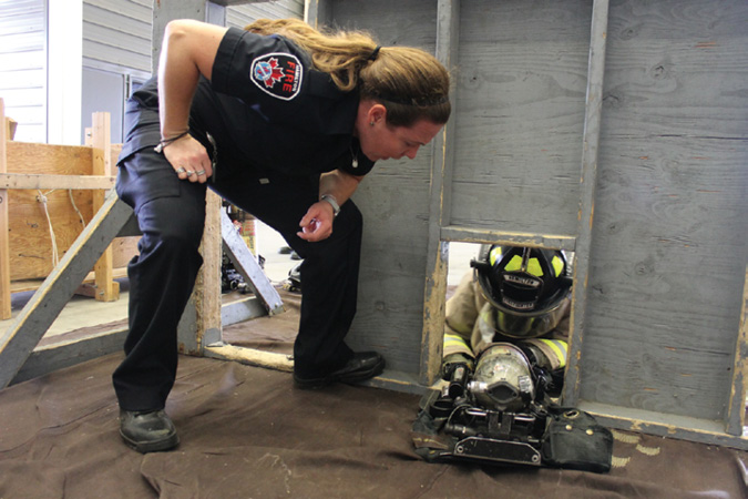 Firefighter Kelly Doyle encourages a recruit through a low-profile obstacle.