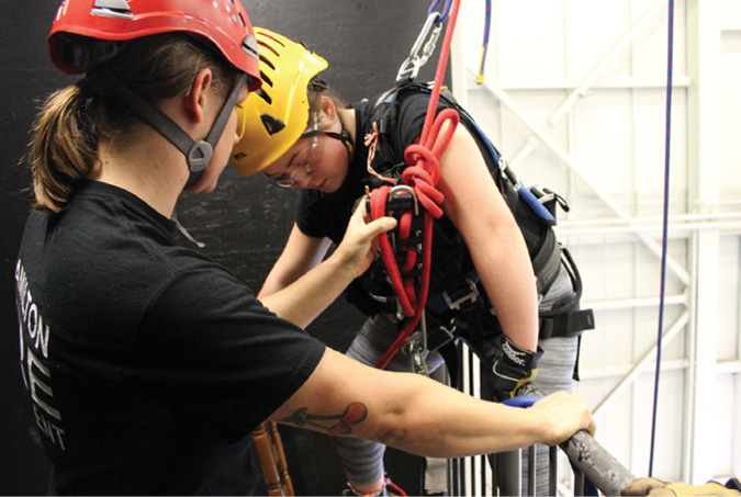 Firefighter Pike Krpan assists a recruit in setting up a rappel.
