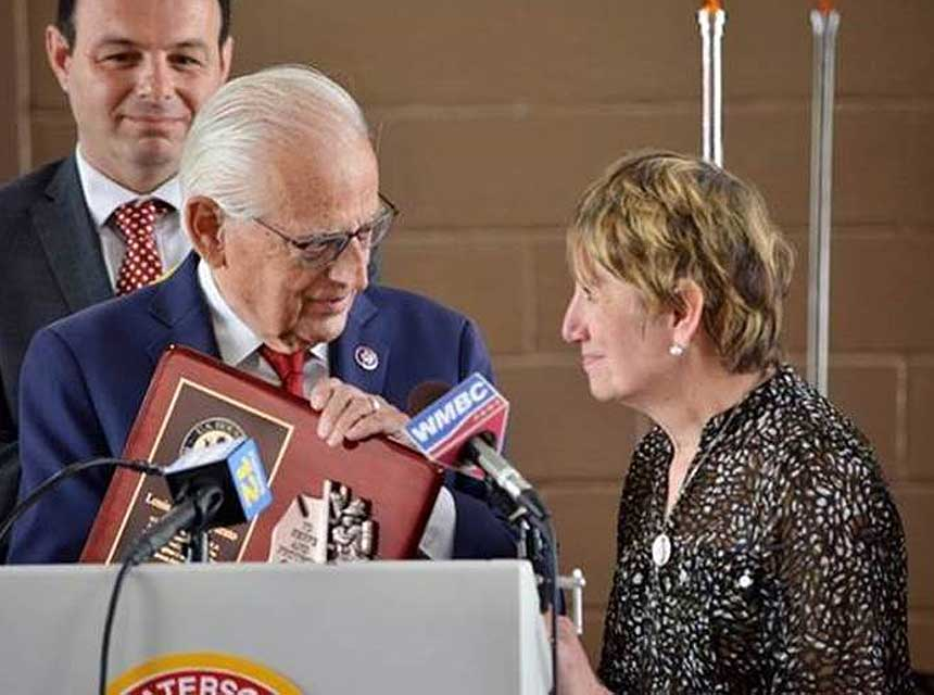 Rep. Pascrell presents a plaque to Marie Imparato, wife of the late Chief Lou Imparato of Passaic City, New Jersey, who played a major role in the crafting of the FIRE Act