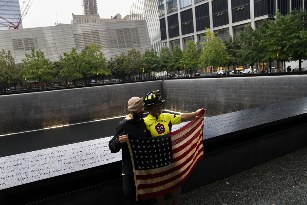 Retired Santa Clara firefighter Darrell Sales, right, and fellow cyclist Jeremy Provancher, left, stand beside the south pool holding an American flag after completing their